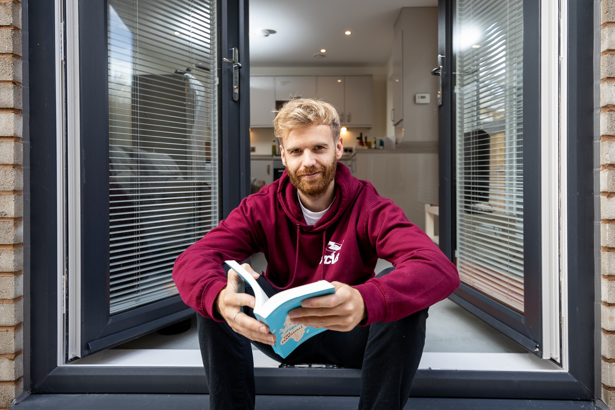 Chris sits on the patio at his shared ownership home in Liverpool